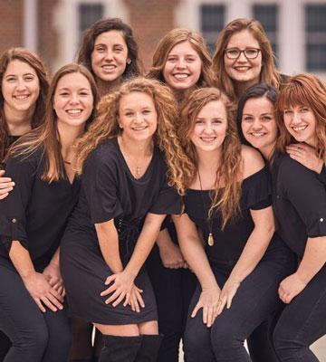 The 9-woman women's a cappella group woven poses near the Will Academic Center