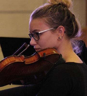 A violinist plays in the Bethel College Philharmonia Orchestra