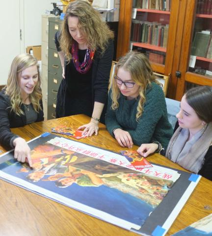 "Students and Rachel Epp Buller work on the exhibit ""Campaign for a New China."""