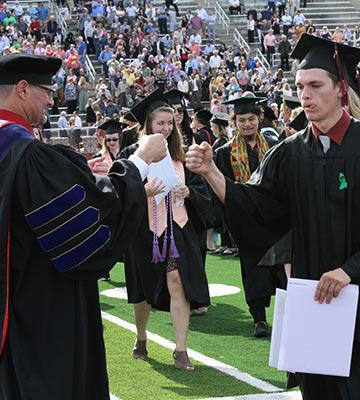 President Gering fist-bumps new graduate Heath Goertzen.