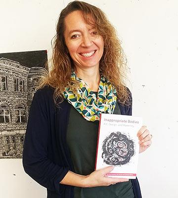 Rachel Epp Buller holds a copy of the book she co-edited, published this fall.
