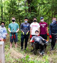 Soccer players spent Service Day rooting out invasive honeysuckle near Kauffman Museum.